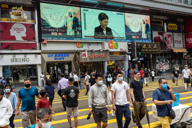 HONG KONG, CHINA - 2021/06/22: Pedestrians wearing facemasks as a precaution against the spread of covid-19 walk past a screen reporting the weekly press conference of Carrie Lam, Hong Kong's chief executive, in Tsim Sha Tsui district. Lam said that foreign governments are beautifying acts that endanger national security in their criticisms of the police crackdown on pro-democracy newspaper Apple Daily, days after five were arrested and assets linked to the newspaper frozen. (Photo by Chan Long Hei/SOPA Images/LightRocket via Getty Images)