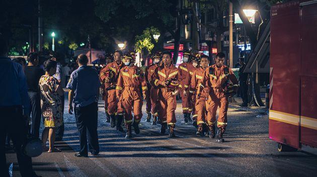 Los rescatistas salen del lugar donde se derrumbó el hotel Four Seasons Kaiyuan en la ciudad de...