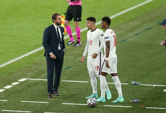 England players Jadon Sancho and Marcus Rashford on the pitch with coach Gareth