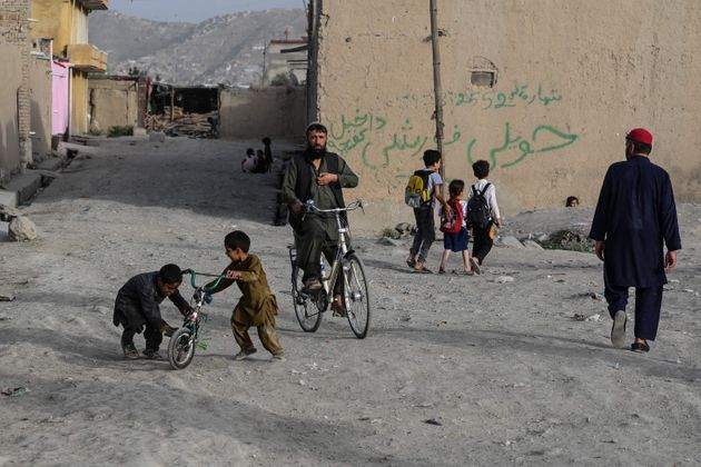 People pass by as children play with a cycle along a road at a residential area in Kabul on July 11, 2021. (Photo by SAJJAD HUSSAIN / AFP) (Photo by SAJJAD HUSSAIN/AFP via Getty Images)