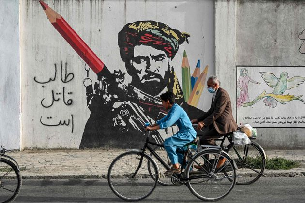 Cyclist peddles past a mural painted on the wall along a road in Kabul on July 11, 2021. (Photo by SAJJAD HUSSAIN / AFP) (Photo by SAJJAD HUSSAIN/AFP via Getty Images)