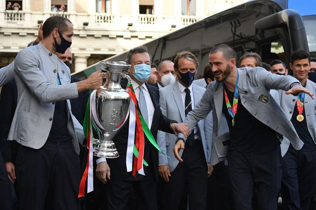 Italy's Prime Minister, Mario Draghi (C) congratulates Italy's defender Leonardo Bonucci (R) as Italy's defender Giorgio Chiellini (L) holds the UEFA EURO 2020 trophy, and Italy's coach Roberto Mancini (Rear C) looks on, as players and staff of Italy's national football team arrive to attend a ceremony at the prime minister's office Palazzo Chigi in Rome on July 12, 2021, a day after Italy won the UEFA EURO 2020 final football match between Italy and England. (Photo by Tiziana FABI / AFP) (Photo by TIZIANA FABI/AFP via Getty Images)