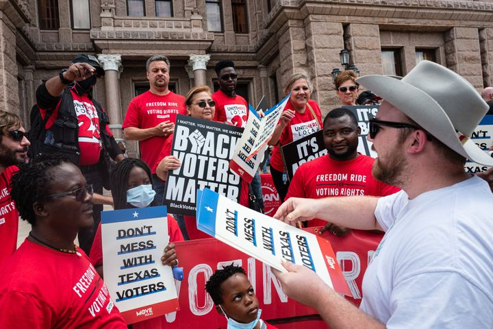 """""""Don't Mess With Texas Voters"""" signs are distributed before the start of a voting rights rally outside of the Texas State Cap"""