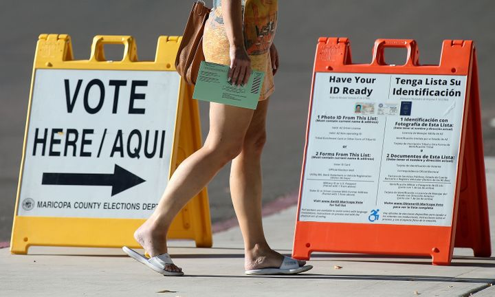 An Arizona voter carries her ballot to a Phoenix polling place to vote in the state's primary on Aug. 28, 2018. Arizona has a