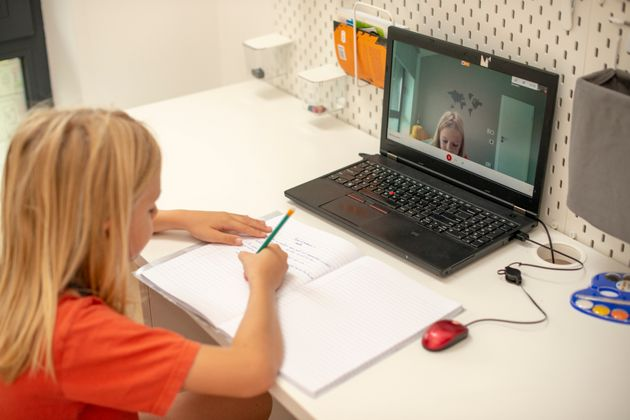 Distance learning online education. A schoolboy boy studies at home and does school homework. A home...