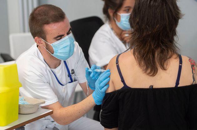 Una joven recibe la dosis de la vacuna contra la covid-19 en el Hospital Enfermera Isabel Zendal de Madrid,...