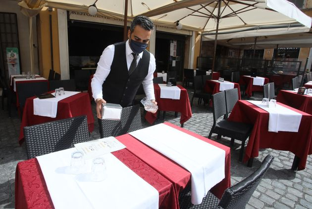 ROME, ITALY - APRIL 29,2021: A waiter sets a table in an open space of a restaurant in Rome, because from Monday 26 April Italy will gradually reopen after six months of rolling virus blocks. (Photo credit should read Marco Ravagli/Barcroft Media via Getty Images)