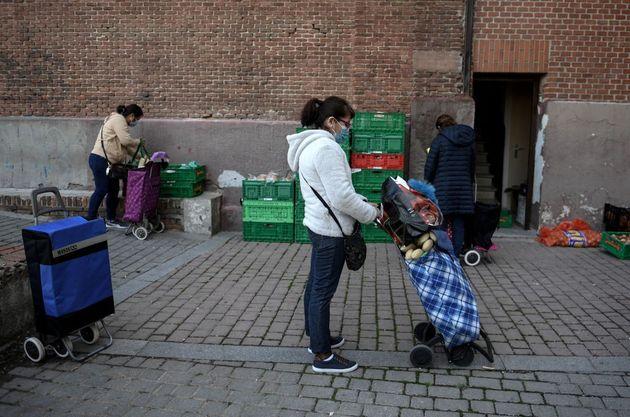 Una mujer espera para recibir comida en Madrid, el pasado 10 de
