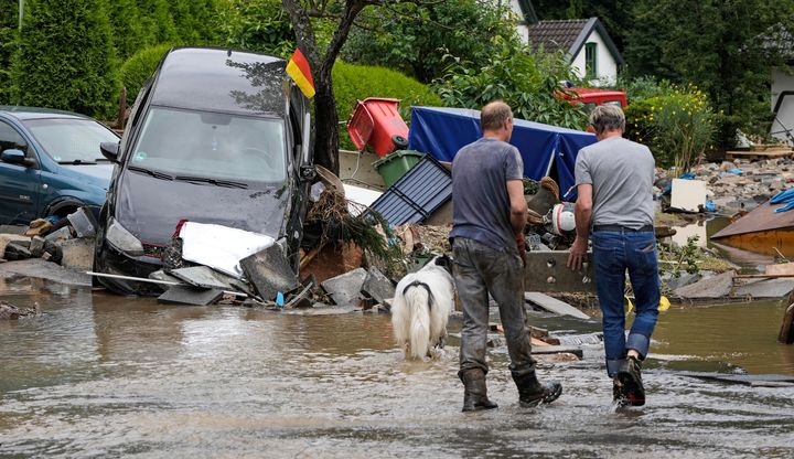 People clean up a street with damaged cars and houses in Hagen, Germany.
