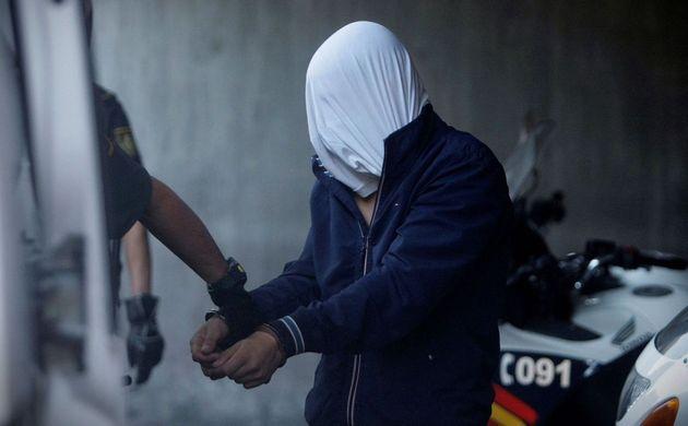 Agentes de la Guardia Civil conducen a uno de los cuatro detenidos por el homicidio de Samuel Luiz al...