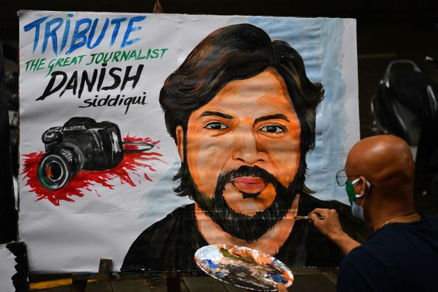 An art teacher gives finishing touches to a painting of Reuters journalist Danish Siddiqui as a tribute outside an art school in Mumbai on July 16, 2021, after the Pulitzer Prize-winning photographer with the Reuters news agency was killed covering fighting between Afghan security forces and the Taliban near a border crossing with Pakistan, the media outlet reported, citing an army commander. (Photo by Indranil MUKHERJEE / AFP) (Photo by INDRANIL MUKHERJEE/AFP via Getty Images)