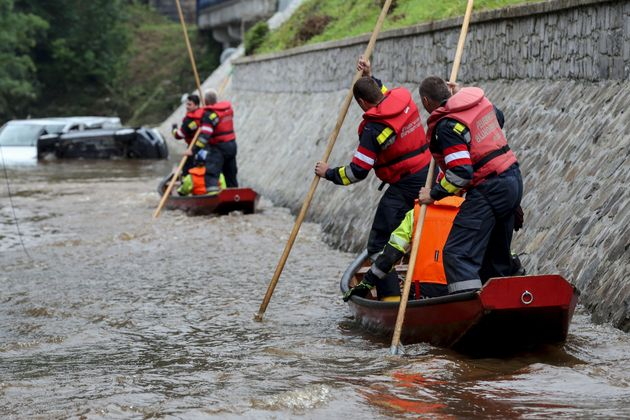 Austrian firefighters steer a boat in a flooded street in Pepinster on July 16, 2021, where the situation...