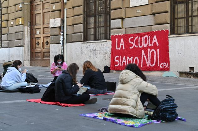 19 November 2020, Italy, Rom: Schoolgirls are sitting in front of their high school, on which a banner with the inscription La Scuola siamo Noi (We are the school) is hanging. They protest against having to teach online and demand a return to face-to-face teaching. The government had introduced so-called homeschooling as a measure in the wake of the Corona pandemic to protect against further infection. Photo: Johannes Neudecker/dpa (Photo by Johannes Neudecker/picture alliance via Getty Images)