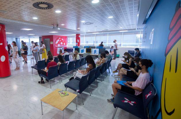 Jóvenes estudiantes esperando para vacunarse antes de irse de