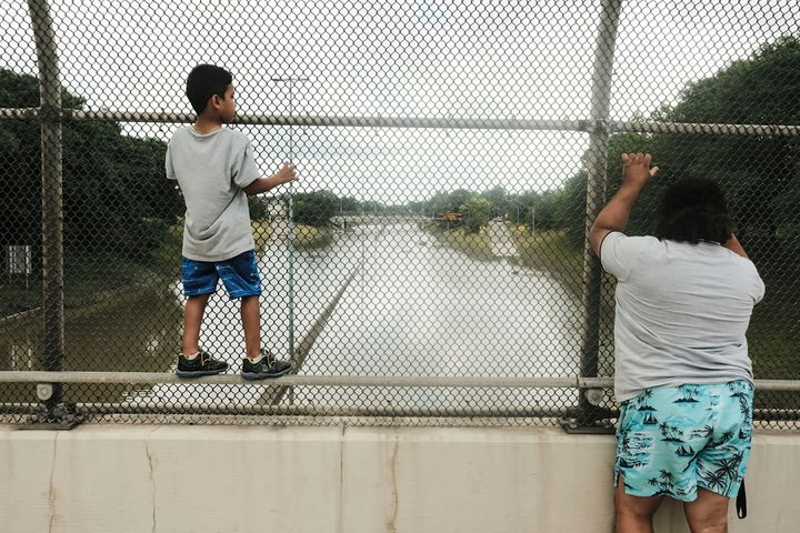 Detroit residents observe a stretch of I-94 under several feet of water after rains flooded parts of Metro Detroit last month