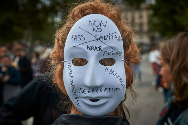 PARIS, FRANCE - JULY 14: Anti-Vaccine protestors gather at Place de la Republique in protest against the new restrictions announced by President Macron on Monday claiming the new measures are a form of apartheid on July 14, 2021 in Paris, France. Starting August 1, people will have to show proof of vaccination or a negative Covid-19 test to access bars, cafes, restaurants, shopping centres, hospitals, long-distance trains and planes. A similar rule will apply to large events from July 21. (Photo by Kiran Ridley/Getty Images)