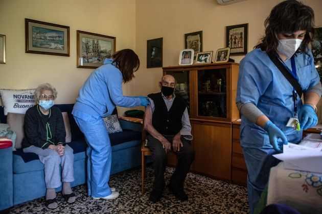 BORGHETTO LODIGIANO, ITALY - MAY 14: Two nurses prepare to administer a second dose of the Pfizer BioNTech vaccine to an elderly couple as they take take part in a door-to-door COVID-19 vaccine campaign for people unable to travel to vaccination centres on May 14, 2021 in Borghetto Lodigiano, near Lodi, Italy. In the last weeks Italy has significantly boosted its vaccination campaign, hitting its target of administering more than half a million jabs in one day and seeing a steady drop of fresh infections and hospitalizations. (Photo by Emanuele Cremaschi/Getty Images)