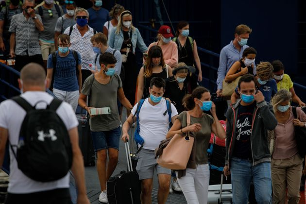 Passengers wearing protective face masks disembark a ferry upon its arrival on the Greek island of Mykonos on October 8, 2020. - The tourism industry in Greece has been hit hard during the Covid-19 pandemic. (Photo by David GANNON / AFP) (Photo by DAVID GANNON/AFP via Getty Images)