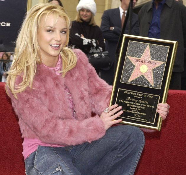 Pop singer Britney Spears holds a replica plaque as she poses for photographers following an unveiling ceremony honoring Spears with the 2,242nd star on the Hollywood Walk of Fame, in Los Angeles, California, November 17, 2003. REUTERS/Jim Ruymen JR/HB