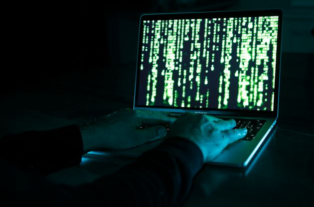 PARIS, FRANCE - DECEMBER 27: In this photo illustration, a hacker with an Anonymous mask on his face and a hood on his head uses a computer on December 27, 2019 in Paris, France. In IT security, a hacker is an IT specialist, who is looking for ways to bypass software and hardware protections. Hackers are generally intelligent programmers who seek to manipulate or modify a computer system or network. (Photo by Chesnot/Getty Images)
