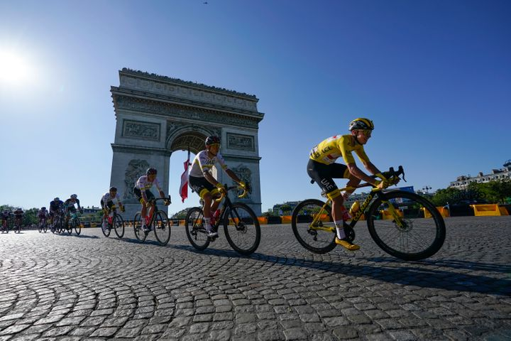 Cyclists pass the Arc de Triomphe during the twenty-first and last stage of the Tour de France cycling race in Paris, France,