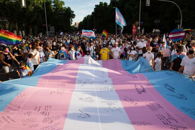 スペイン・マドリードで開かれたプライドパレードで、トランスジェンダーフラッグを広げて囲む人々(2021年7月3日)