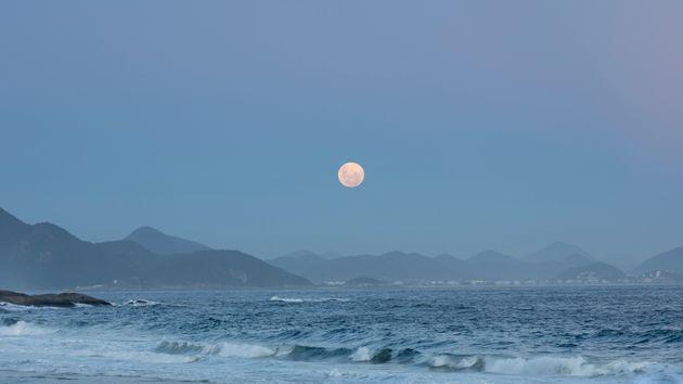 Rio de Janeiro, Brazil - February 8, 2020: View of the full moon rising above the mountain range