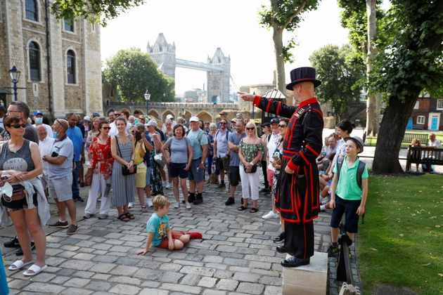 A Yeoman Warder, Barney Chandler gestures as he leads the first