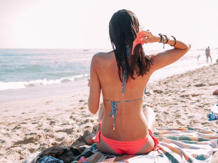 Una mujer peinándose en la playa