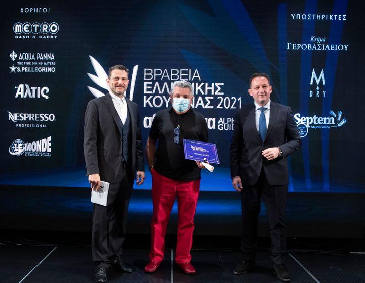 """Το """"Varoulko Seaside"""" αναδείχθηκε για μια ακόμη χρονιά καλύτερο εστιατόριο με ελληνική κουζίνα στη χώρα με 16/20 (Αθήνα). Το βραβείο στον Λευτέρη Λαζάρου, ιδιοκτήτη και σεφ του εστιατορίου, απένειμε ο Αναπληρωτής Υπουργός Εσωτερικών Στέλιος Πέτσας, παρουσία του master of ceremony της απονομής Γιώργου Καραμίχου."""