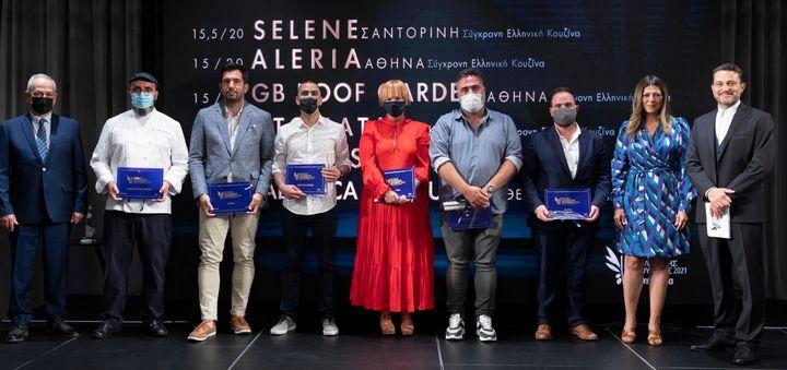 """Τα Βραβεία Ελληνικής Κουζίνας με βαθμολογία 15/20 και 15,5/20 παρέλαβαν οι (από αριστερά) Άλκης Σωτηρίου, γενικός διευθυντής """"Makedonia Palace"""" και Σωτήρης Ευαγγέλου, executive σεφ """"Salonica Restaurant"""" (Θεσσαλονίκη, 15/20), Γκίκας Ξενάκης, σεφ """"Aleria"""" (Αθήνα, 15/20), Νίκος Μαυρόκωστας, σεφ """"GB Roof Garden"""" (Αθήνα, 15/20), Γεωργία Δώδου, marketing """"Sani Resort"""" για το """"Ντομάτα"""" (Χαλκιδική, 15/20), Τάσος Στεφάτος, σεφ """"Petra Restaurant"""" (Σαντορίνη, 15/20) και ο Κωνσταντίνος Σιγάλας, media & web performance executive """"Katikies"""" για το """"Selene"""" (Σαντορίνη, 15,5/20). Τη βράβευση έκανε η Υφυπουργός Τουρισμου Σοφία Ζαχαράκη. Στην σκηνή μαζί τους και ο παρουσιαστής της βραδιάς Γιώργος Καραμίχος."""