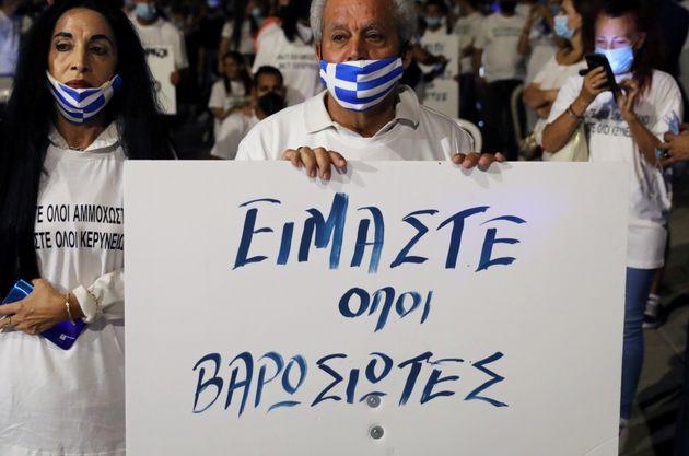 Διαδηλωτής κρατάει πλακάτ στο οδόγραγμα της Δερύνειας σε συγκέντρωση διαμαρτυρίας πριν από το