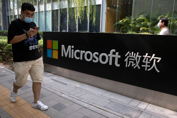 A man looks at his smartphone as he walks by the Microsoft office in Beijing, China on Friday, Aug. 7, 2020. (AP Photo/Ng Han