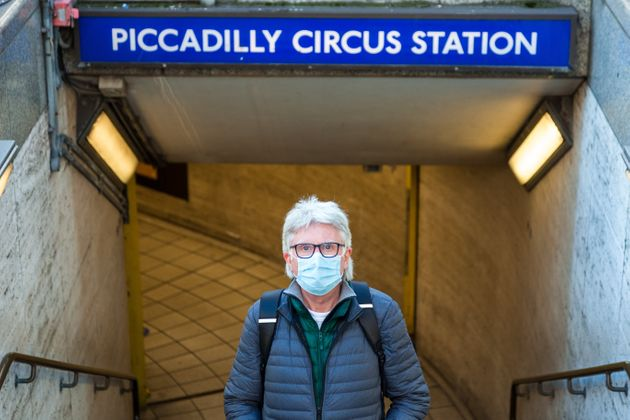 Close up color image depicting a senior caucasian male in his 60s wearing a protective face mask in the city during the coronavirus pandemic. The man is standing in the street outside Piccadilly Circus London underground station, and the architecture and lights of the city of London are defocused beyond. Room for copy space.