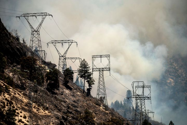 Smoke billows behind power lines as the Dixie Fire burns along Highway 70 in Plumas National Forest, Calif., on Friday, July
