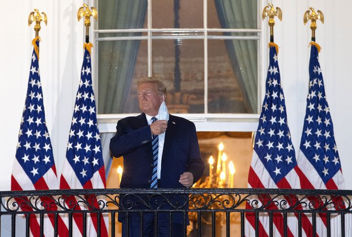 President Donald Trump removes his mask upon return to the White House from Walter Reed National Military Medical Center on O