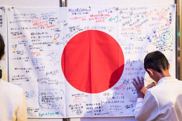 Un niño escribe un mensaje de apoyo sobre la bandera japonesa en una ceremonia por los Juegos...