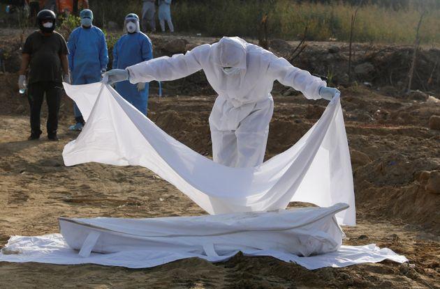 Un membre du personnel soignants recouvrent le corps d'une victime du Covid à New Dekhi le 11...