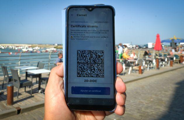 Un QR code, pièce maitresse du pass sanitaire sur un téléphone portable devant un...