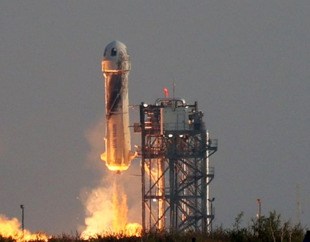 Blue Origin's New Shepard lifts-off from the launch pad carrying Jeff Bezos along with his brother...