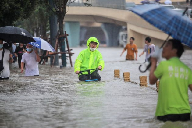 TOPSHOT - This photo taken on July 20, 2021 shows a man riding a bicycle through flood waters along a...
