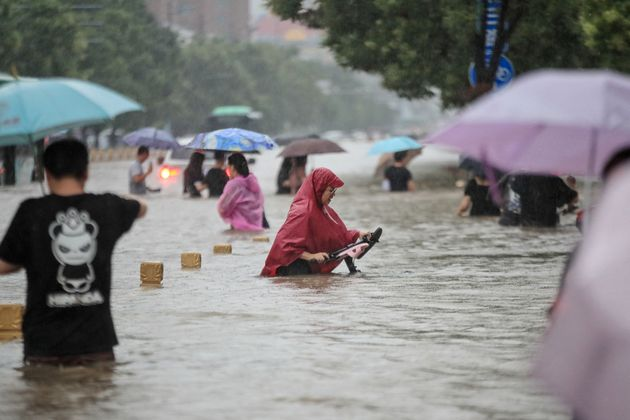 TOPSHOT - This photo taken on July 20, 2021 shows people wading through flood waters along a street following...