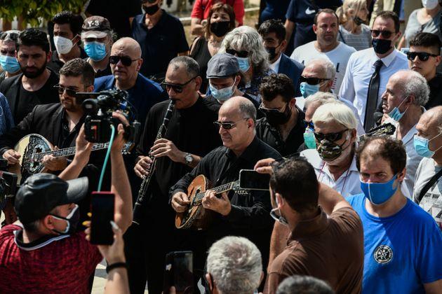 Ο δεξιοτέχνης του μπουζουκιού Μανώλης Καραντίνης (πρώτος από δεξιά), που είχε συνοδεύσει τον Τόλη Βοσκόπουλο επί σειρά ετών σε εμφανίσεις του -και στη συναυλία του Ηρώδειο- αποχαιρετά τον Τόλη Βοσκόπουλο.