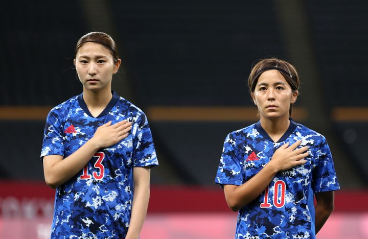 SAPPORO, JAPAN - JULY 21: (L - R) Yuzuho Shiokoshi #13 and Mana Iwabuchi #10 of Team Japan stand for the national anthem prior to the Women's First Round Group E match between Japan and Canada during the Tokyo 2020 Olympic Games at Sapporo Dome on July 21, 2021 in Sapporo, Hokkaido, Japan. (Photo by Masashi Hara/Getty Images)