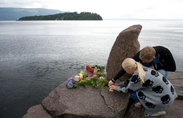 A woman and a man light candles in honor of the victims of the July 22 shooting spree at a Labour Party...