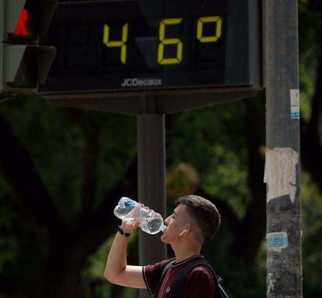 Un hombre bebe agua junto a un termómetro que marca 46º durante un día de alerta roja por altas temperaturas,...