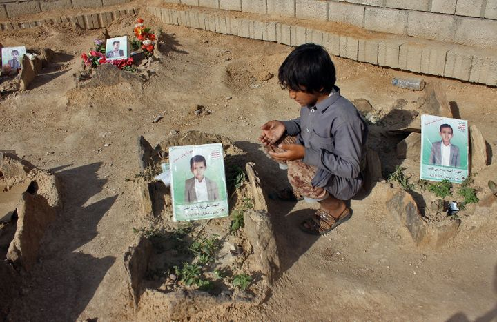 A Yemeni child at the graves of schoolboys who were killed in an August 2018 airstrike by a military coalition that included the UAE.