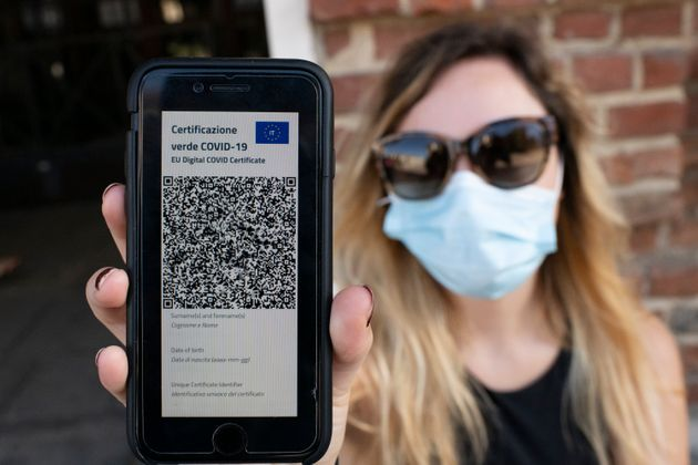 TURIN, ITALY - JUNE 30: A woman shows Italy's Covid-19 Green Pass for post-vaccine travel on a smartphone...