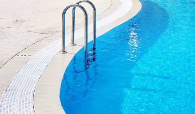 A minimalist view of curves in a swimming pool featuring the arched hand rails and