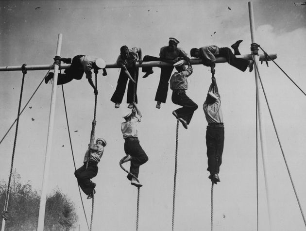 12th September 1934: Sailors from the training ship 'Warspite', climbing ropes during their sports day...